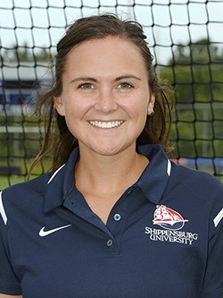 Photo of Tara Zollinger who has brown hair and brown eyes smiling while wearing a blue shippensburg university shirt in front of a field hockey goalie net
