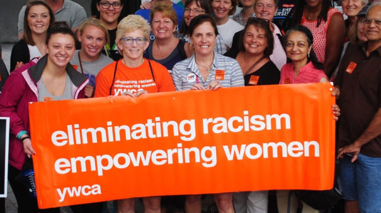 women marching with a ywca banner